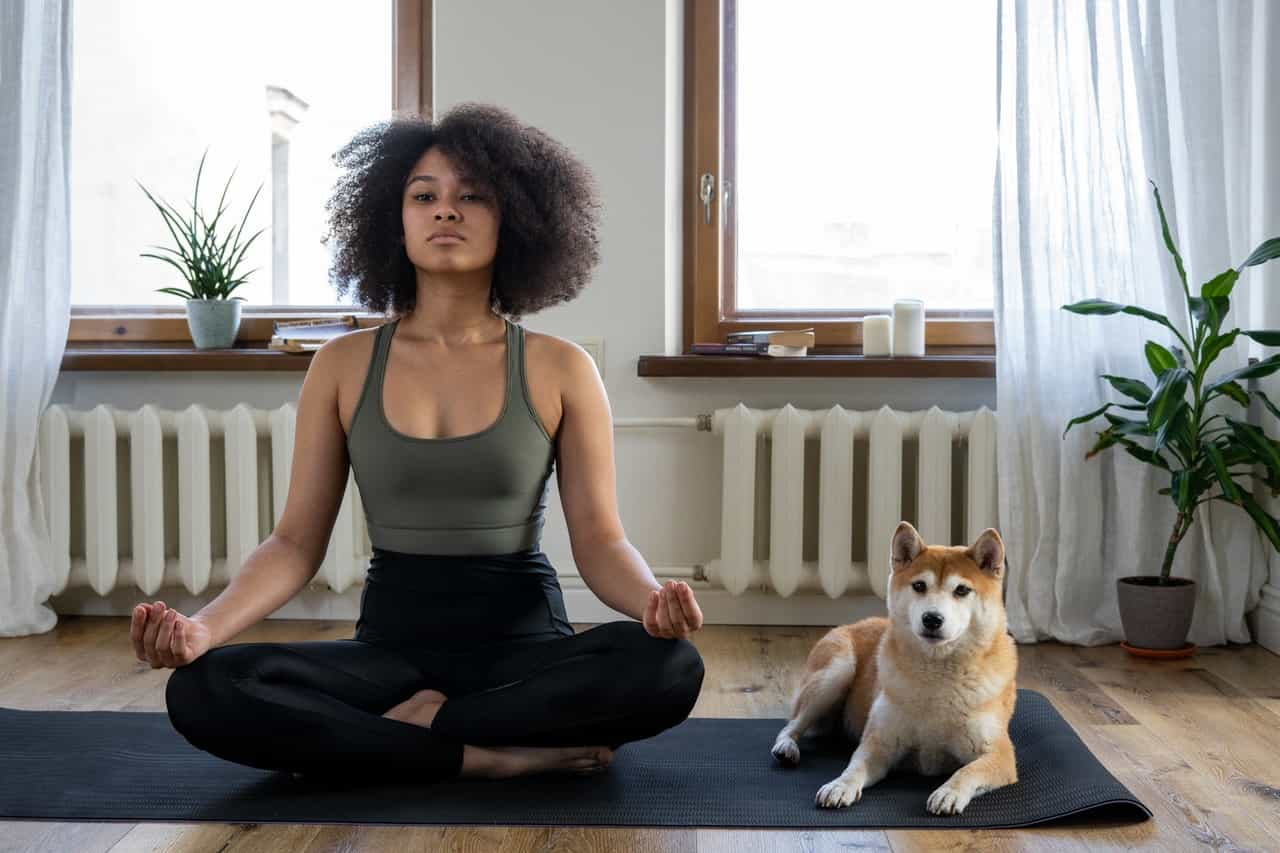 woman meditating with her dog beside her